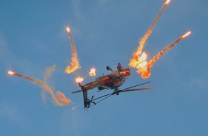 Boeing AH-64D Apache c/n DN017 with tailnumber Q-17 of the Royal Netherlands Air Force with the 2011 livery of the Apache Solo Display fires flares during the Open Days of the Dutch Air Force on 17 September 2011 over Leeuwarden air base in The Netherlands (EHLE).